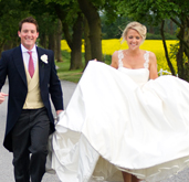 A bride and groom taking a romantic stroll down the majestic drive at Sywell Grange